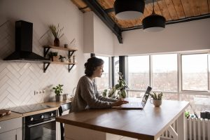 woman typing on laptop in kitchen