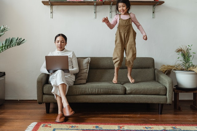 mom typing on laptop on couch with daughter jumping beside her