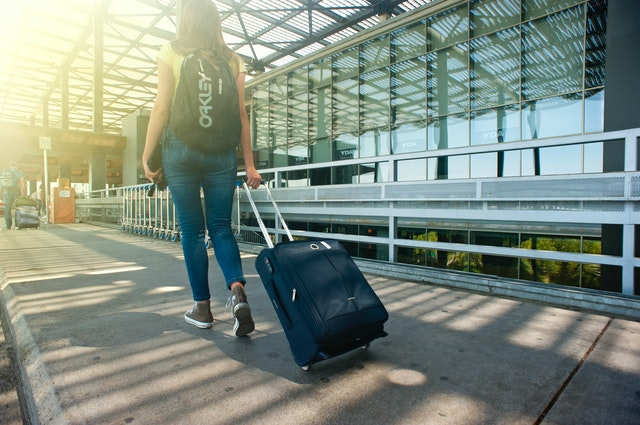 woman rolling suitcase at airport