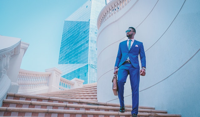doctorpreneur wearing suit and holding briefcase, standing outside on steps