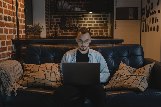 man working at computer on couch